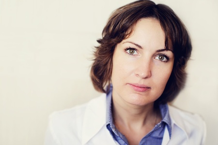 Portrait of a female doctor against a white wall photo