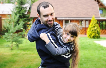 Father plays with his daughter holding her in his arms photo