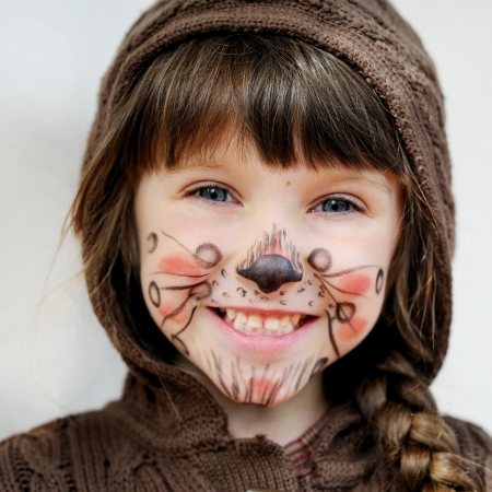 female face closeup: Cute little girl with face painted wearing knit brown hood