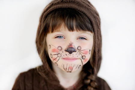 painting face: Cute little girl with face painted wearing knit brown hood