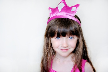 cute little girl smiling: Portrait of beautiful little girl in pink tiara, isolated Stock Photo