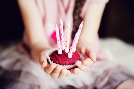 Close-up photo of a cupcake with five candles in childs hands photo