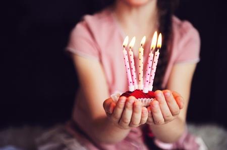 velas de cumplea�os: Close-up foto de una magdalena con cinco velas encendidas en las manos del ni�o Foto de archivo