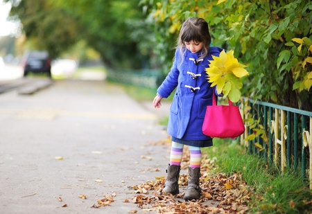Funky little girl in blue coat walking down the street with bunch of leaves and pink bag Stock Photo