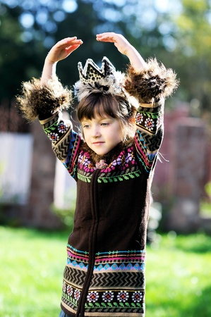 Adorable child girl wearing colorful coat with hands over her head