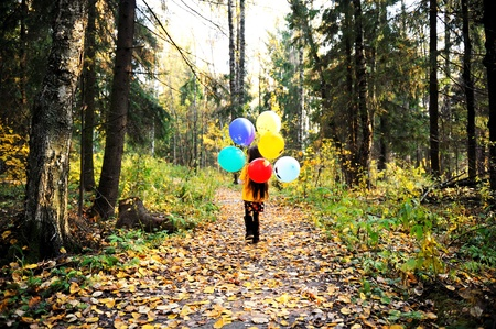 fun colors: Child girl with colorful balloons walking alone in autumn forest