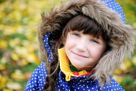 Outdoor portrait of cheerful little girl in blue coat with a hood
