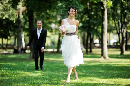 Elegant brunette bride posing outdoors with a bouquet on her wedding day Stock Photo