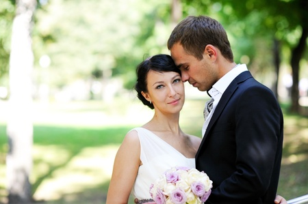 Elegant bride and groom posing outdoors in the park photo