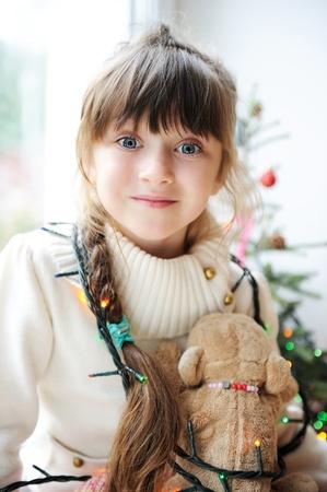 przewidywanie: Cute little girl w oczekiwaniu na wakacje zdobione choinki w tle Zdjęcie Seryjne