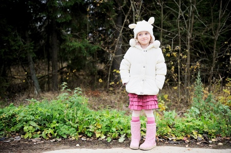 Full length portrait of coquette child girl wearing warm white hat, focus on face photo