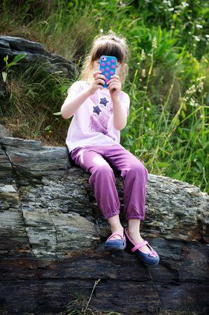 Niña sentada en las rocas con el teléfono móvil de tomar instantáneas