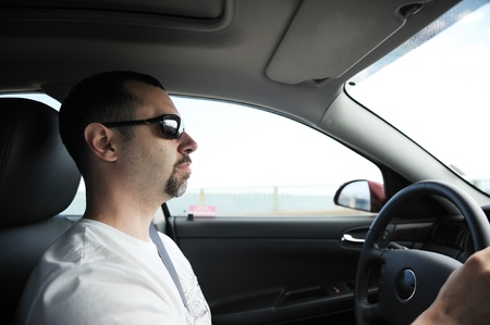 Concentrated man in sunglasses driving passenger car during the day photo