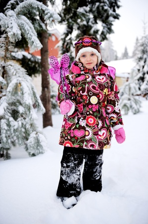 Adorable little girl in colorful snow suit with fairy wings and magic wand plays outdoors in snowfall photo
