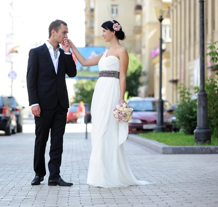 Groom kissing brides hand outdoors in the street