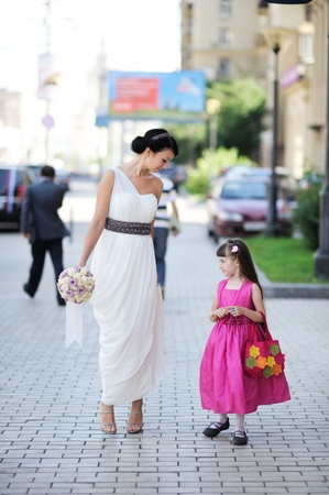 flowergirl: Beautiful bride posing together with flowergirl princess
