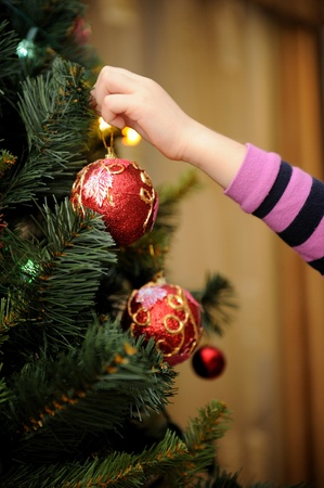 home decorating: Little girl decorating the Christmas tree (focus on ball)