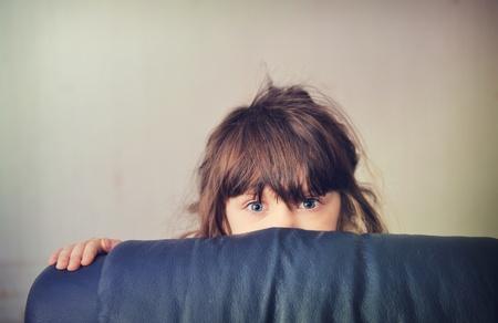 mojado: Ni�a que juega a las escondidas detr�s del sof� cama Foto de archivo