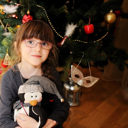 Close-up portrait of smiling little girl sitting with a toy under Christmas tree photo