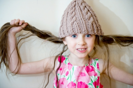 Portrait of a child girl with long hair wearing beige knitted hat
