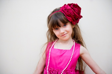 Pretty little girl in beautiful pink dress with flower headband, isolated Stock Photo - 11488716