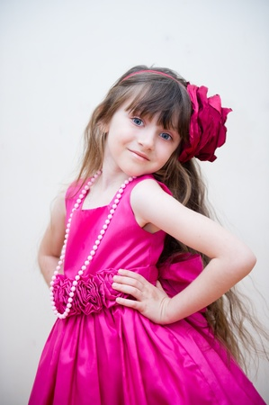 little girl posing: Pretty little girl in beautiful pink dress with flower headband, isolated Stock Photo