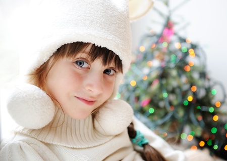 Cute little girl in anticipation of the holiday with decorated Christmas tree in the background photo
