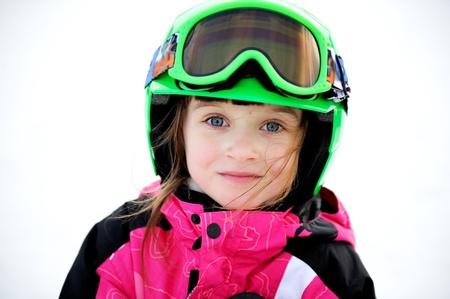 Portrait of smiling little child girl in ski helmet and googles photo