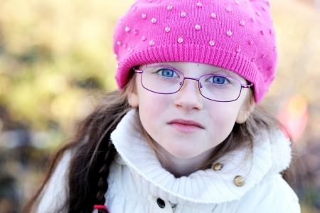 A portrait of little girl in glasses wearing pink cap
