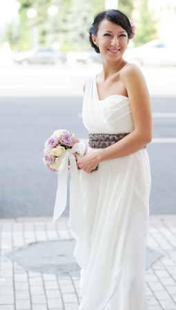 Elegant brunette bride posing outdoors with a bouquet on her wedding day photo