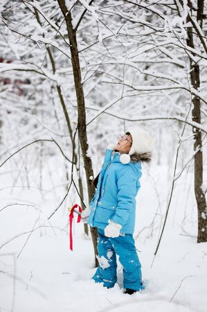 Adorable little girl walking in snow winter forest photo