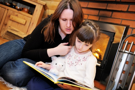 Mother and daughter reading a book in front of fireplace Stock Photo - 11960603