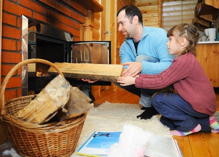 Father and daughter putting a log into fireplace photo