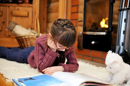 Child girl is reading a book in front of fireplace photo