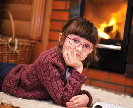 Portrait of a child girl lying in front of fireplace with her chin propped up by the hand photo