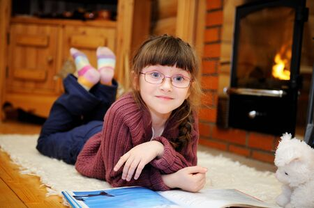 Child girl is reading a book in front of fireplace Stock Photo - 11960602