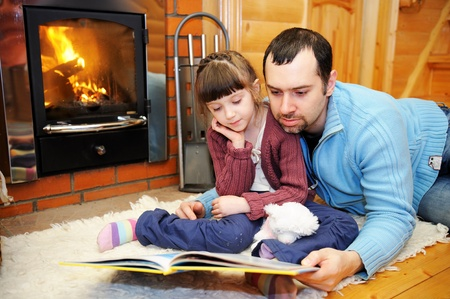 warm home: Father and daughter reading a book in front of fireplace Stock Photo