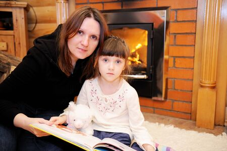 Mother and daughter reading a book in front of fireplace photo