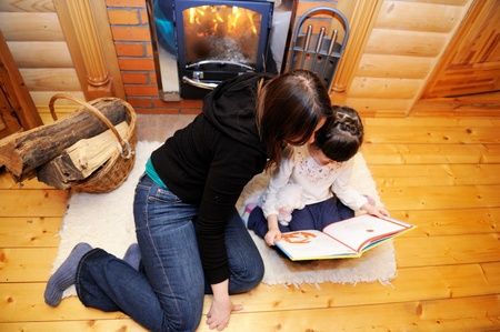 fire place: Mother and daughter reading a book in front of fireplace, top view Stock Photo