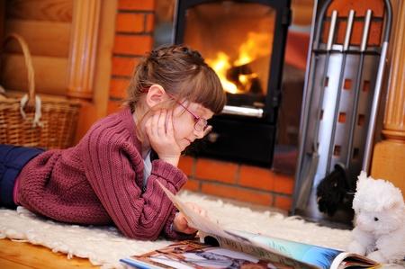incendio casa: Niño chica está leyendo un libro frente a la chimenea Foto de archivo