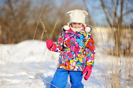 Toddler girl in colorful snowsuit plays in snow on sunny winter day photo