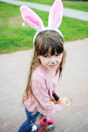 pretender: Portrait of cute little girl with painted nose and bunny ears