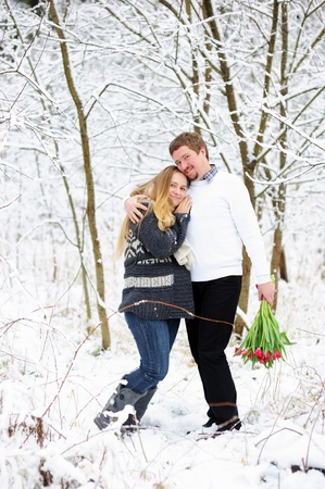 Beautiful pregnant woman walking with her husband in snow forest photo