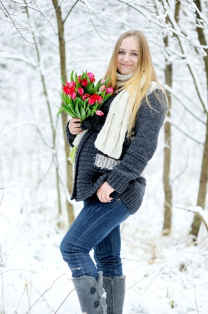 snow flowers: Beautiful pregnant woman posing with flowers in snow forest Stock Photo
