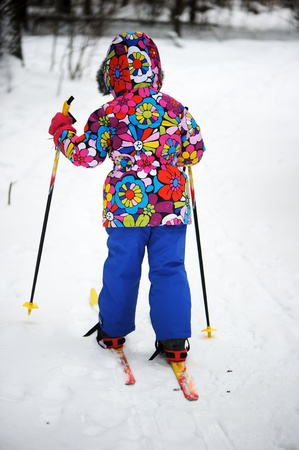 sports wear: Toddler girl in colorful snowsuit skiing on a bright winter day