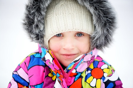 Portrait of toddler girl in colorful snowsuit on bright winter day photo