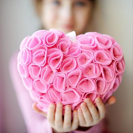 Retrato de niña bonita celebración toddelr corazón de color rosa suave