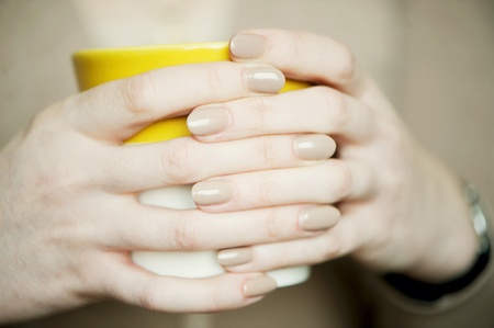 Female hands with soft beige manicure holding a cup photo