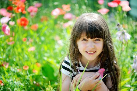 one little girl: Smiling little girl with long dark hair sitting on poppy field