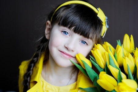 Portrait of a sunny child girl with bouquet of yellow tulips on a dark background photo
